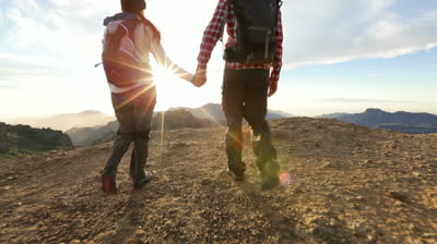 stock-footage-couple-holding-hands-hiking-outdoors-at-romantic-sunset-hikers-man-and-woman-lovers-trekking